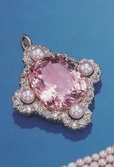 A late Victorian pink sapphire, diamond and pearl pendant, Howard & Co., circa 1900. The cushion-shaped pink sapphire weighing approximately 25 carats within a frame of quatrefoil shape set with old European-cut diamonds and quartered by 4 pearls, mounted in platinum and gold, signed Howard & Co. Source: Sotheby's, Magnificent Jewelry, NY, October 1993.