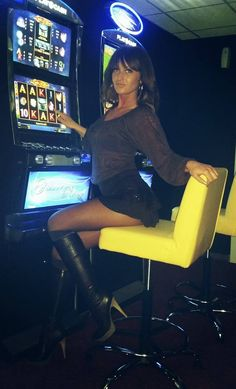 Pretty girl in black top and mini skirt and long boots playing video games-----------long legs