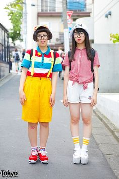 16-year-old Shinatsu (right): Gingham shirt with white shorts, both of which were picked up resale. Her backpack is from Spinns. She is also wearing a wings ring and platform sandals with striped tube socks and a USA bucket hat. 17-year-old Sato (left): Striped polo t-shirt with suspender bermudas, both resales, and platform sneakers from WEGO. Her accessories are resales as well, and they include a fruit print cap, star hair pin and brooch, and a panda backpack.