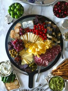 Entertaining antipasto platter for dinner party with pickles, olives, chocolate, pesto, cheese, dried fruit, crackers and dip