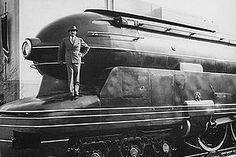 Raymond Loewy stands on Pennsylvania Railroad S1 6-4-4-6 Steam Locomotive (1939).