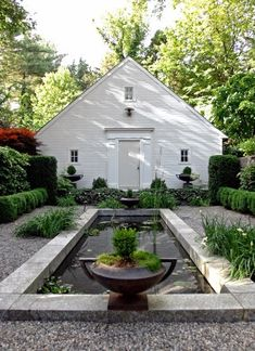 White on White Outbuilding overlooking a Reflecting Pool.