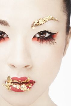 annaham:    [Description: Photo of a young Asian woman wearing elaborate makeup. She wears flakes of gold leaf on her eyebrows and lips, along with red eyeshadow, false lashes on her bottom lids, and red-orange lipstick.]