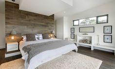 chambre à coucher moderne en couleurs neutres avec literie en blanc et gris, tapis beige clair et déco murale en bois