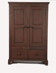 """PAINTED CUPBOARD. Attributed to Pennsylvania, 1st half-19th century, pine. Two raised-panel doors and two drawers, and resting on bracket feet. Retains a wonderful, old, dry, red paint. Minor imperfections. 76 1/2""""h. 49 1/2""""w. 17 1/2""""d."""