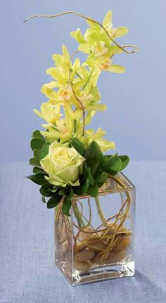 Flower Arrangement Ideas....I would use real flowers and opaque vase or Hosta leafs to conceal roots........