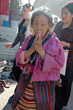 Elder Tibetan Woman, Bodhisattva Day, with her hands in prayer mudra, wearing traditional apron and wrap, malas, two Buddhist women, Tharlam Monastery, Boudha, Kathmandu, Nepal, via Flickr.