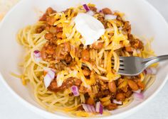 This Turkey Chili Spaghetti is a bowl full of comfort food. Turkey chili full of spices and veggies, served on a bowl of spaghetti with all chili toppings.