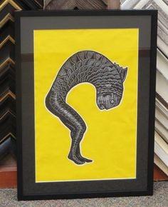This simple black on black frame design makes the yellow background really pop! #blockprint #customframing