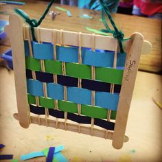 Weaving loom made from popsicle sticks and rubberbands. Cheap and easy and fun!