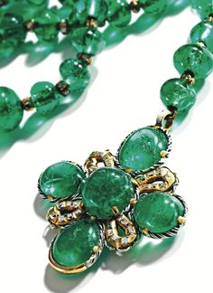 EMERALD, DIAMOND AND ENAMEL ROSARY, GERMAN, LATE 17TH CENTURY Composed of 70 emerald beads spaced by gold rondelles set with table-cut diamonds, suspending a pendant set with five double-cabochon emeralds and numerous table-cut diamonds, within gold surrounds applied with black and white enamel, length 17 inches including the pendant.