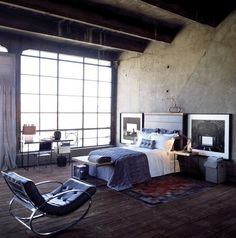 This Zara Home loft space offers stripped-down appeal. Raw cement walls and exposed wood ceiling beams are balanced with textured bedding, a cosy rug, modern furniture and large-scale art.    Photographer: Zara Home  Source: House & Home January 2009 issue  Products: Bedding, Zara Home.