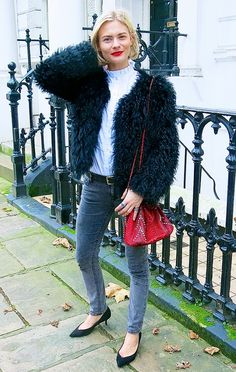Pandora Sykes wears a furry black jacket with a white turtleneck, jeans, and a bold red bag.