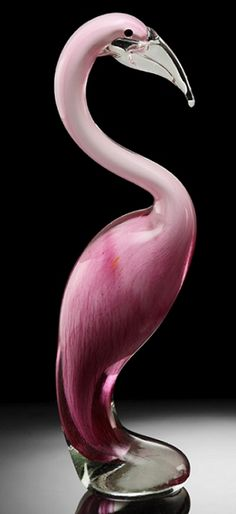 Art Glass Demure Pink Flamingo Sculpture, Stohans Showcase. Contemporary style glass Pink Flamingo that stands with its neck slightly retracted and beak turned down. The Flamingo sculpture is a simplistic design created from solid pink glass with a casting of clear glass on top. The footed base of the Flamingo is heavily rounded and flares out for stability. The Flamingo's beak is clear glass and it has small round black eyes.