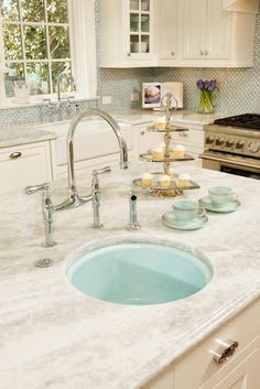 "The countertops are quartzite ""white princess"".The ""antiqued"" finish on this particular slab (it is also often referred to as ""leathered"") is very good at concealing imperfections...and crumbs!"
