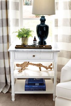 White, open nightstand with shelves and a marble top. A dark indigo blue lamp on top and horizontal striped curtains.