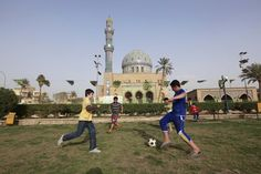 Iraq youngsters play soccer in central Baghdad in March. Hadi Mizban/AP