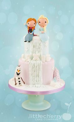 This Fabulous Frozen cake was made by Little Cherry Cake Company. Anna and Elsa are sitting side by side on top the cake on either side of a frozen icy ...