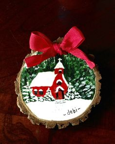 Rustic hand painted Christmas ornament on walnut wood slice. Little red country church in the snow.