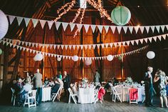 Hudson Valley Wedding in a barn. love the lighting above, paper lanterns, bunting white table and chairs.  via:ruffledblog.com