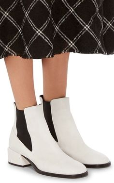 This **Tibi** bootie features a calf leather body with a rounded toe, a matching block heel and stretch detailing.
