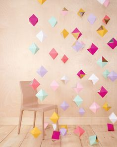 """If you've got an afternoon (and a few willing bridesmaids), you can whip up this cheery backdrop for your photo booth, ceremony marker, guest-book table—or wherever your venue is in need of a little pick-me-up. Make some of these multifaceted beauties, thread them onto string or monofilament, and voilà! Décor is served.    Bonus Tip: To make your garlands really shine, cut a triangle from metallic foil paper to cover one side of each diamond and attach with double-sided tape (""""Mirr..."""