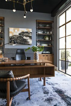 The owner's home office has custom brass and walnut built-ins that house a collection of machine parts. The walls are upholstered in grayish blue flannel, while Heidi Bonesteel designed the midcentury desk with a return that has shallow bookshelves in fro