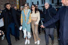 Gigi Hadid wearing denim vest tartan jacket denim button shirt and Bella Hadid wearing cropped top and jacket silk pants seen outside Alberta...