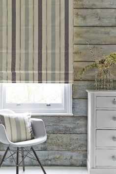 Use distressed wood and white furniture with a mix of grey and blue stripes to create a nautical effect. Our made to measure Stewart Charcoal Roman blind is perfect to add that finishing touch this would look great in both a living room and a bedroom.