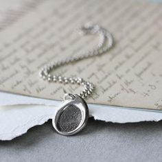 Inked Fingerprint Teardrop Charm on a Silver Chain - The silver is oxidised so you will be able to see the unique loops, whorls and arches of each of the individual and unique fingerprints. You decide how many prints you would like to capture, one or two, side by side.