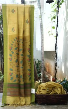 THE LUSTROUS MUSTARD YELLOW MATKA SILK CALCUTTA DHAKAI SAREE HAS MULTICOLOURED WEAVE ON THE ORGANZA PALLU AND FLORAL BHUTAS ALL OVER THE BODY MAKES THE SAREE EVEN MORE SPECTACULAR.