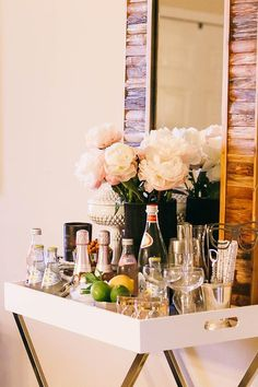 Dining room bar boasts an x based tray table, West Elm Tall Butler Tray Stand, with white lacquer tray top filled with libations along with a reclaimed wood mirror. Bar Cart Styling, Bar Cart Decor, Bar Tray, Trays, Butler Tray, Drink Cart, Beverage Cart, Drinks Trolley, Gold Bar Cart
