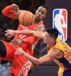 Dwight Howard #12 of the Houston Rockets (L) and Jeremy Lin of the Los Angeles Lakers go after a rebound during the Lakers first regular season NBA game,October 28, 2014 at Staples Center in Los Angeles, California.  AFP PHOTO / Robyn BeckROBYN BECK/AFP/Getty Images