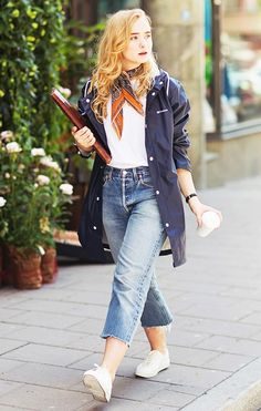 A white top is tucked into boyfriend jeans and paired with a windbreaker, tennis shoes and a silk scarf.