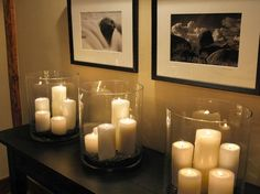Big lighting bang-for-the-buck Dollar-Store pillar candles and hurricane glasses. Love this look!.