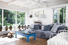 Un sofá cubierto con alfombras indias que se han teñido en un salón con grandes ventanales que dan al jardín ...