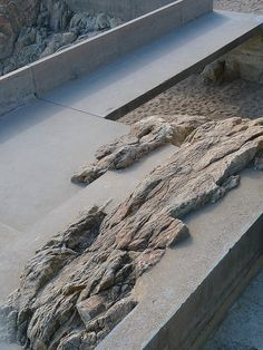 Outcropping of rock embedded in concrete - Alvaro Siza. Pinned to Garden Design - Paving & Stairs by Darin Bradbury.