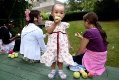 Khine Nein Thazin, 1, from Burma, eats a freshly picked apple at Drew Gardens.