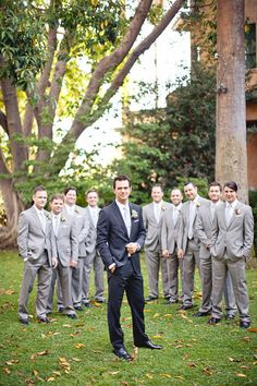 The groom in a classic looking dark blue suit with black shoes and the groomsmen in a more neutral color to match the bridesmaid dresses....peach or taupe dresses or what ever color you choose.  :)
