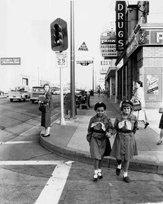 In the midst of the racial segregation era, two 10-year-old Girl Scouts in Montebello, California show the proper way to cross a street, 1955.