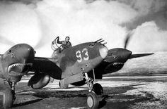 Ten Herb Hasenfus from the 54th Fighter Squadron standing in the cockpit of his P-38 Lightning during heating of motors in Adak, Alaska, Mar 1943. Note the art at the bottom of the engine cover