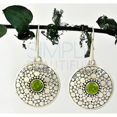 Our Peridot Shield Sterling Silver Earrings - These earrings are round in shape and have a single silver band outlining the earrings. Inside that band is a pattern of polished silver circles with a backdrop of oxidized silver to highlight the detailing. Where the pattern stops, there is a circle of silver beads which frames the centerpiece of the jewelry, a round facet cut green peridot.  http://simplybeautiful2012.com/peridot-shield-sterling-silver-earrings.html#