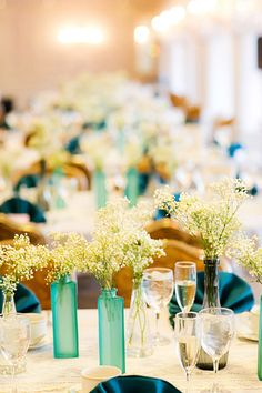Ikea vases w/ baby's breath double as decor and wedding favors.