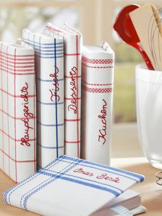 dressing up cookbooks in dishtowels, with the name embroidered on the back. lovely!