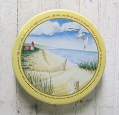 Vintage Hersheys Kisses Candy Tin dated 1992. Hersheys Traditions Series IV. Perfect beach shades for re-purposing lid to for wall hanging - magnet attaches. I count 9 large seashells around the sides.  Pretty scene of a lighthouse by the ocean with the following inspirational quote: The heart is like the sea, It is subject to storms, Ebb Tide and floods, And in its depths is many a precious pearl. signed H. Heine  7 1/4 diameter 2 5/8 tall  Condition: Nice glossy surface allover clean…