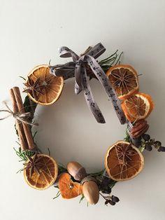 Mustikanvarvuista sidottu kranssipohja, jossa koristeena kuivatut appelsiinikiekot, kaneli ja tähtianis, tammenterhot, pähkinät.