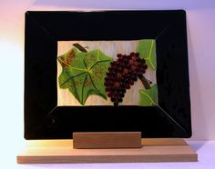"""In A Vineyard A big panel made of fused glass.  I created a black frame of opal glass and the inner part was made on a semi-transparent glass, painted by hand. The leaf is made of green opal glass and embellished with glass frites. In order to make the grapes more shining and more obvious I made them of transparent glass beads and fused them very lightly so they """"come out"""" of the picture making a great and vivid impression.   Measures approx. 18"""" X 18"""""""