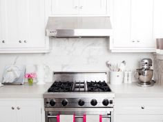 Chunky white quartz counters pair with a gorgeous marble tiled backsplash.
