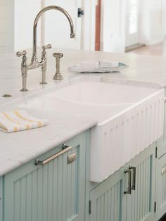 Charming Farmhouse Sink  Grooves on the apron-front sink echo the lines of the blue beaded-board cabinets, creating gorgeous, unexpected texture. The island's farmhouse sink is teamed with a vintage-style bridge faucet and flanked by two pairs of dishwasher drawers.