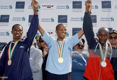 South African marathon runner,Hendrik Ramaala (C) the winner of the Bombay International Marathon 2004 holds the hands of second place winner Kenyan Julius Sugut (R) and third place winner Tanzania's Lucian Timobos (L) on a winners rostum in Bombay, 15 February 2004. Ramaala won in a time of 2.15.47 secs. with Sugut on 2.16.36 secs. and Timobos in a time of 2.16.50 secs.. Some twenty thousand runners participated in the 42km marathon, 21km half marathon and the 7km dream run running through…